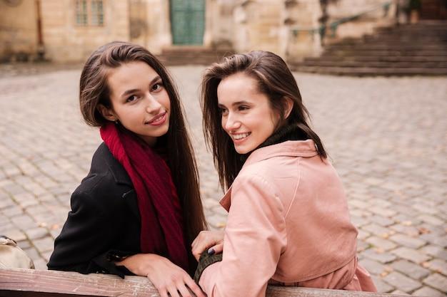 Retrato de dos hermosas mujeres jóvenes felices sentados juntos en el casco antiguo