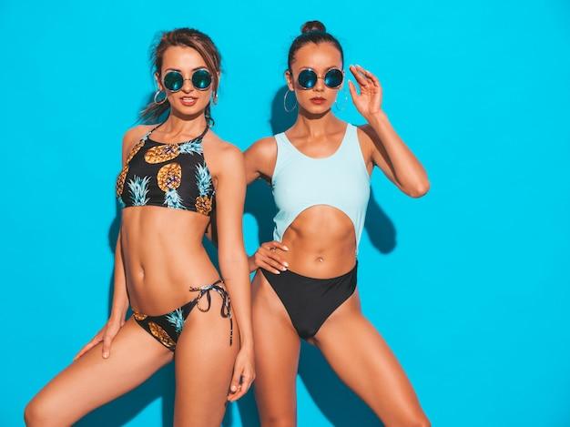Retrato de dos hermosas mujeres sonrientes sexy en trajes de baño de verano. modelos calientes de moda divirtiéndose. chicas con gafas de sol aisladas en azul