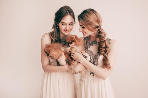 Retrato de dos hermosas mujeres con sus mascotas
