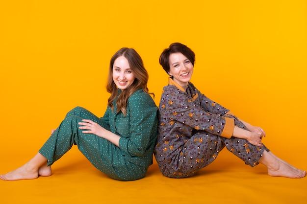 Retrato de dos hermosas niñas vistiendo pijamas coloridos divirtiéndose durante la pijamada aislado
