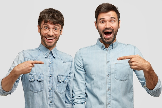 Retrato de dos hombres alegres indican con los dedos índice el uno al otro, felices de comprar nuevas chaquetas de mezclilla