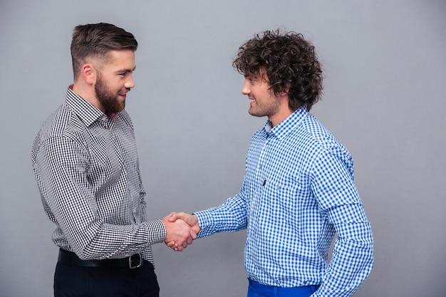Retrato de dos hombres casuales haciendo apretón de manos sobre pared gris