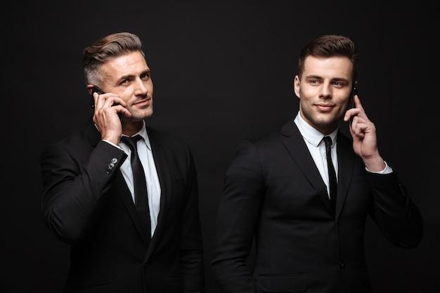 Retrato de dos hombres de negocios sonrientes vestidos con traje formal posando a la cámara y hablando por teléfonos celulares aislados sobre pared negra