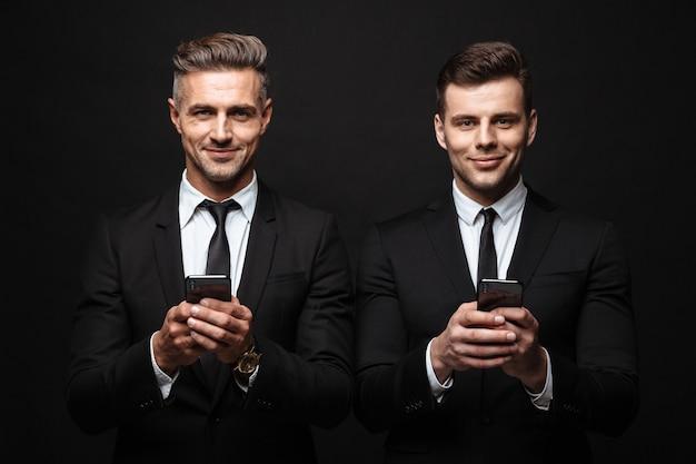 Retrato de dos hombres de negocios sonrientes vestidos con traje formal posando a la cámara con teléfonos móviles aislados sobre pared negra