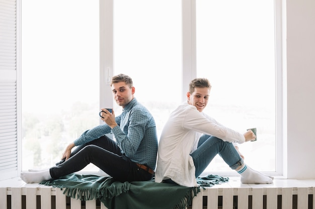Retrato de dos hombres que sostienen la taza de café que se sienta cerca de ventana