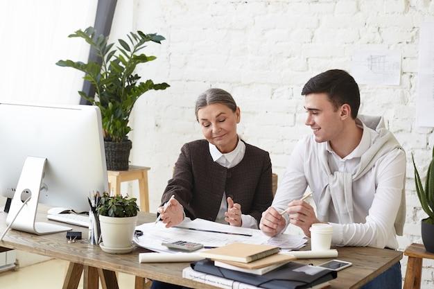 Retrato de dos ingenieros caucásicos felices, talentoso joven y mujer madura, jefe de intercambio de ideas, discutiendo los planes de construcción del proyecto de vivienda residencial juntos, sentados en el escritorio de oficina