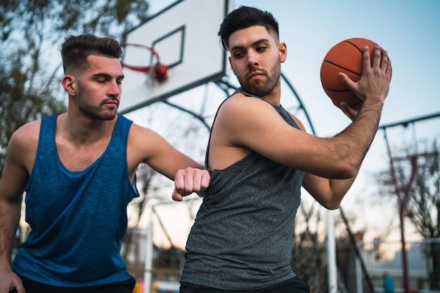 Retrato de dos jóvenes amigos jugando baloncesto y divirtiéndose en la cancha al aire libre. concepto deportivo.