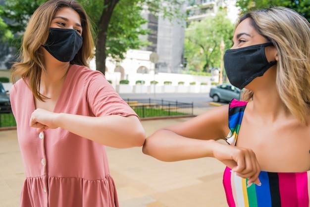 Retrato de dos jóvenes amigos con mascarilla y golpeando los codos al aire libre.