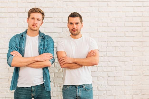 Retrato de dos jóvenes amigos varones con sus brazos cruzados de pie contra la pared blanca