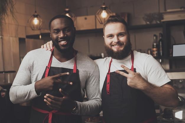 Retrato de dos jóvenes baristas masculinos en el espacio de trabajo