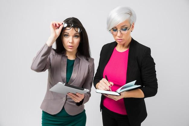 Retrato de dos jóvenes damas de negocios en trajes aislados sobre fondo