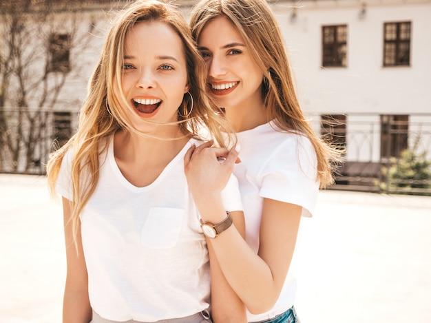 Retrato de dos jóvenes hermosas rubias sonrientes chicas hipster en ropa de moda verano camiseta blanca. . modelos positivos divirtiéndose.