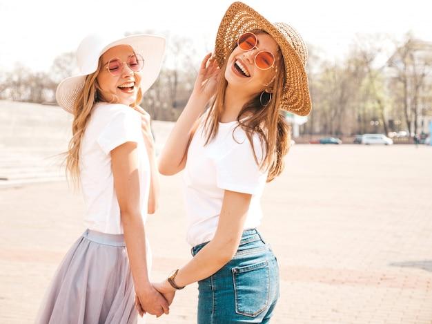 Retrato de dos jóvenes hermosas rubias sonrientes chicas hipster en ropa de moda verano camiseta blanca. . modelos positivos tomados de la mano