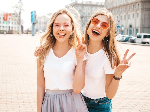 Retrato de dos jóvenes hermosas rubias sonrientes chicas hipster en ropa de moda verano camiseta blanca. mujeres despreocupadas sexy posando en la calle. modelos positivos que muestran signos de paz y lengua