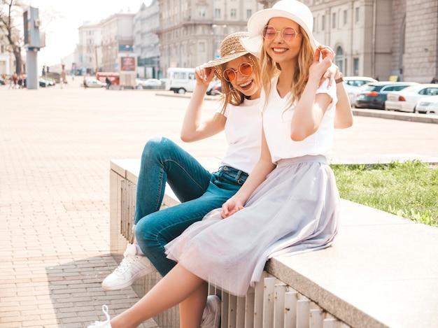 Retrato de dos jóvenes hermosas rubias sonrientes chicas hipster en ropa de moda verano camiseta blanca. .