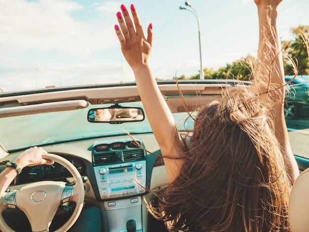 Retrato de dos jóvenes hermosas y sonrientes chicas hipster en coche descapotable