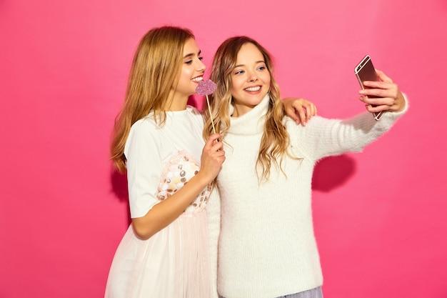 Retrato de dos jóvenes mujeres rubias sonrientes con estilo