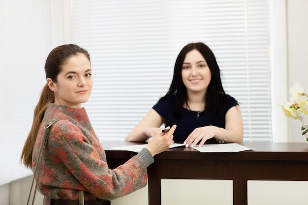Retrato de dos jóvenes mujeres sonrientes. administrador de clinica dental y paciente