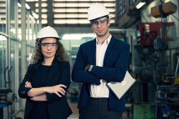 Retrato de dos maquinistas está de pie con confianza con casco de seguridad frente a la pared de vidrio de la fábrica de la industria.