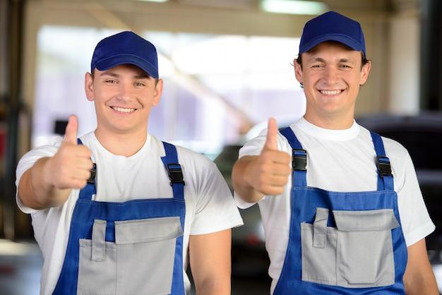 Retrato de dos mecánicos masculinos en servicio de reparación de automóviles