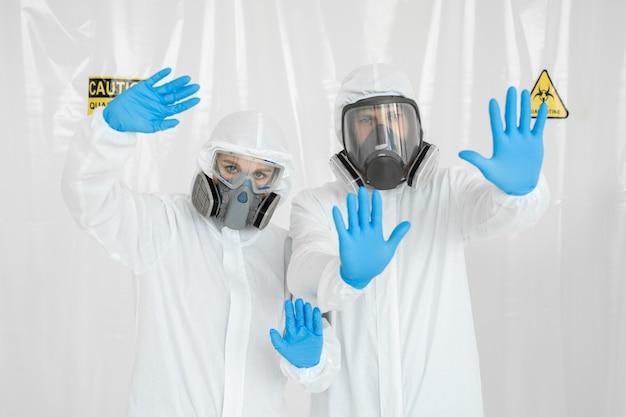 Retrato de dos médicos, un hombre y una mujer en uniforme médico con una mascarilla protectora y una mano enguantada mostrando una señal de stop. detener el concepto covid-19. la epidemia de coronavirus.