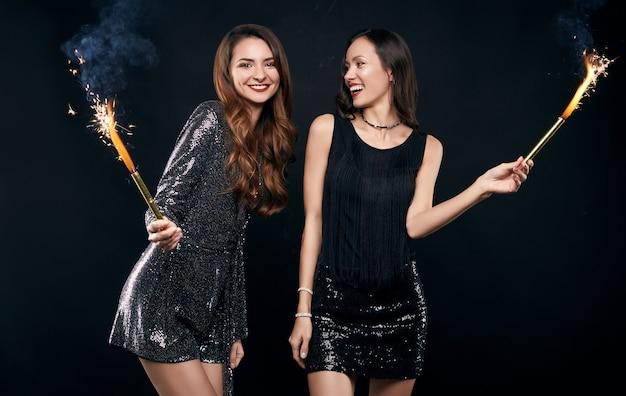 Retrato de dos mejores amigas bastante locas en vestidos de moda posando con fuegos artificiales