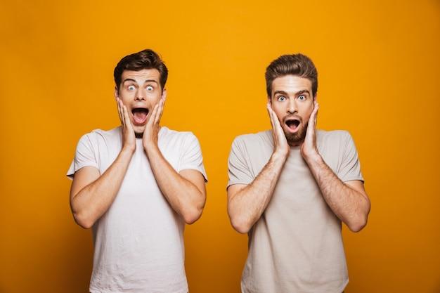 Retrato de dos mejores amigos sorprendidos de los hombres jóvenes