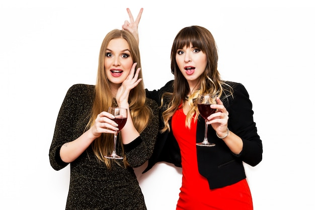 Retrato de dos mejores amigos en traje de noche posando y bebiendo vino