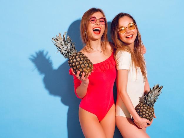 Retrato de dos modelos de morenas sonrientes de moda en ropa de traje de baño de verano. chicas con piñas frescas. mujer con gafas de sol redondas divirtiéndose y posando