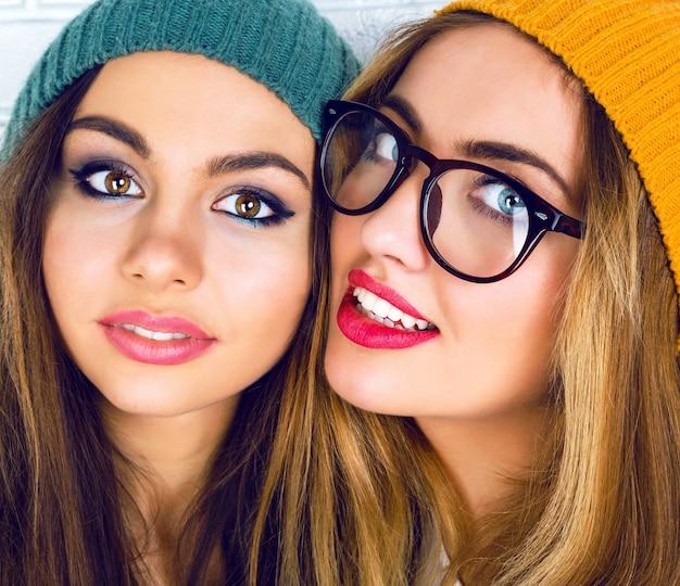 Retrato de dos muchachas bonitas con maquillaje brillante, sombreros y gafas