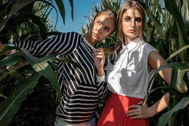 Retrato de dos muchachas rubias en ropa de moda y con estilo, entre el follaje de un campo de maíz.