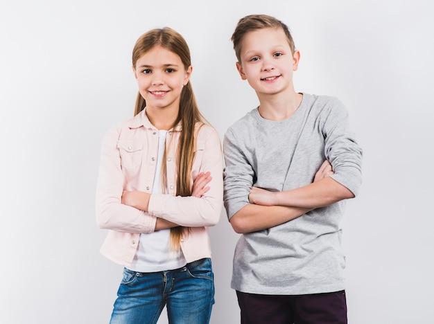 El retrato de dos el muchacho y la muchacha sonrientes con sus brazos cruzaron la mirada a la cámara contra el fondo blanco