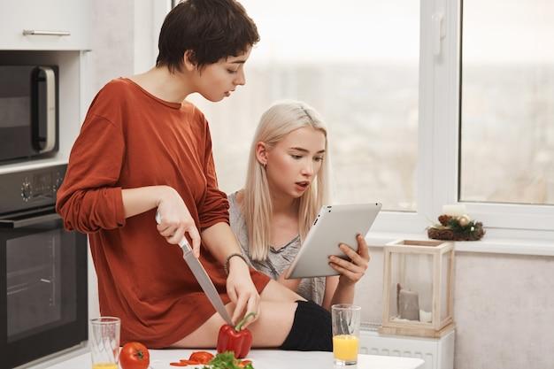 Retrato de dos mujeres atractivas que se sientan en cocina y que leen algo en tableta, expresando curiosidad e interés mientras preparan la ensalada. las niñas pasan la prueba de lo bien que se conocen