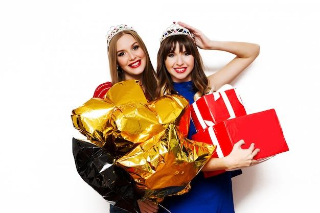 Retrato de dos mujeres bonitas con globos de fiesta brillantes y cajas de regalo