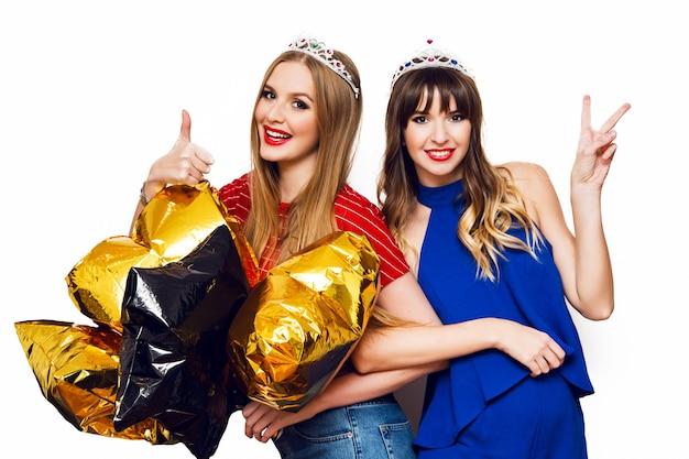 Retrato de dos mujeres bonitas con globos de fiesta brillantes