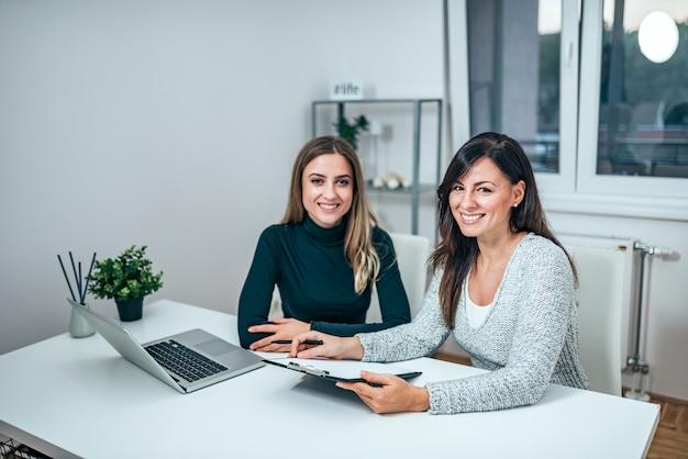 Retrato de dos mujeres empresarias casuales trabajando. mirando a la camara