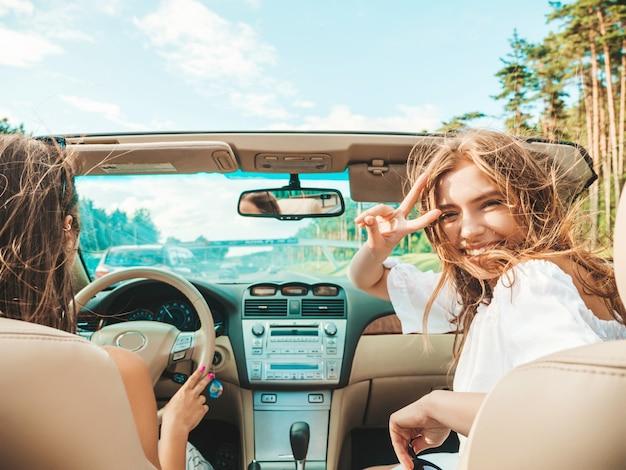 Retrato de dos mujeres hipster hermosa y sonriente joven en coche descapotable