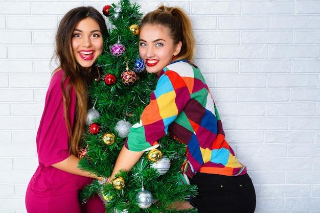 Retrato, de, dos, mujeres jóvenes, se abrazar, un, árbol de navidad