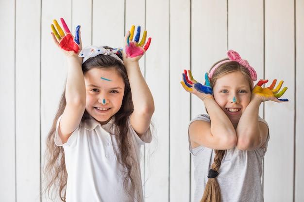 Retrato de dos niñas levantando sus manos mostrando las manos pintadas mirando a la cámara