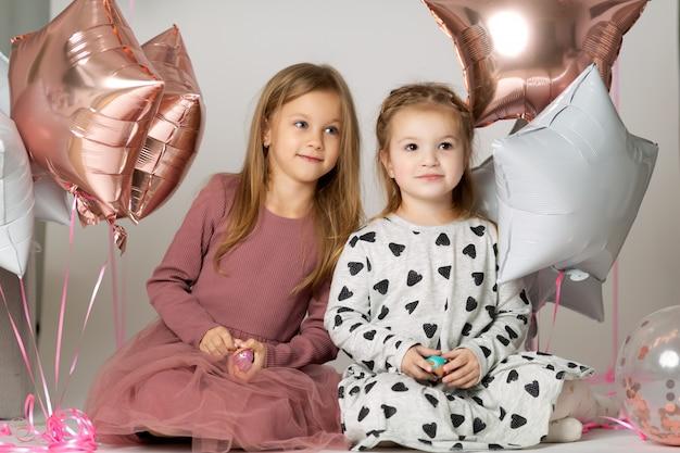 Retrato de dos niñas lindas sentados en el suelo con globos