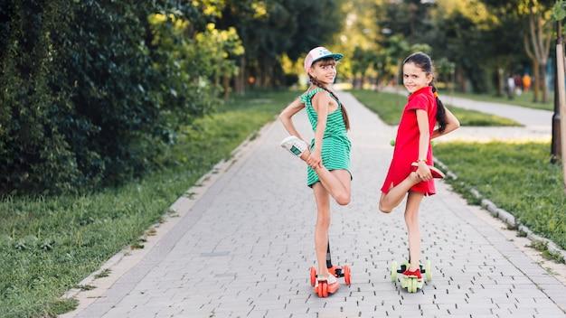 Retrato de dos niñas de pie sobre una pierna sobre el patinete en el parque