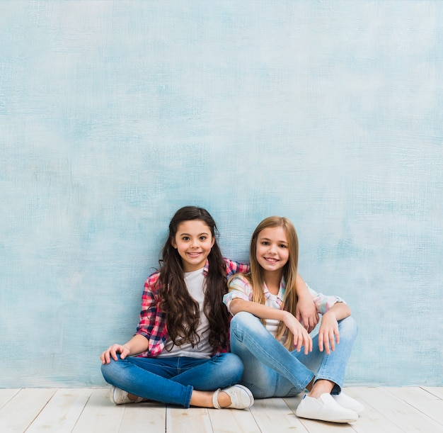 Retrato de dos niñas sonrientes sentados juntos contra la pared azul pintada