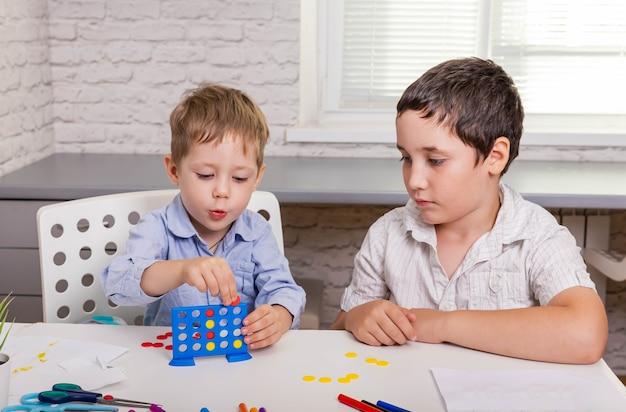 Retrato de dos niños alegres sonriendo y jugando juntos al juego de mesa en la mesa en casa.