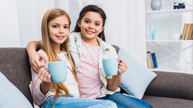 Retrato de dos niños femeninos sentados juntos en el sofá sosteniendo tazas de café en la mano