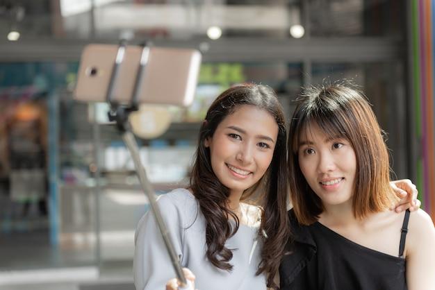 Retrato de dos novias sonrientes alegres haciendo una selfie en el centro comercial.