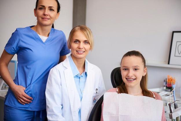 Retrato de dos ortodoncistas sonrientes y niño en el consultorio del dentista