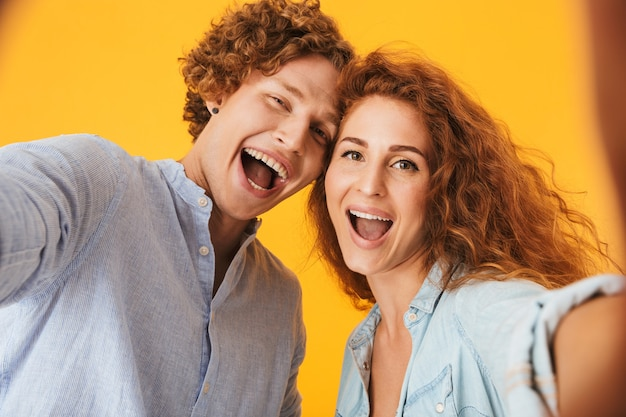 Retrato de dos personas felices, hombre y mujer, riendo y tomando fotos selfie, aislado sobre fondo amarillo