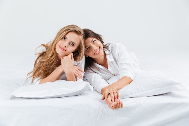 Retrato, de, dos, sensual, mujer joven, acostado, juntos, en, cama blanca