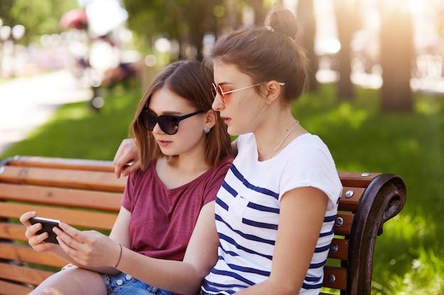 Retrato de dos tiernas chicas sentadas en un banco en el espacio verde local