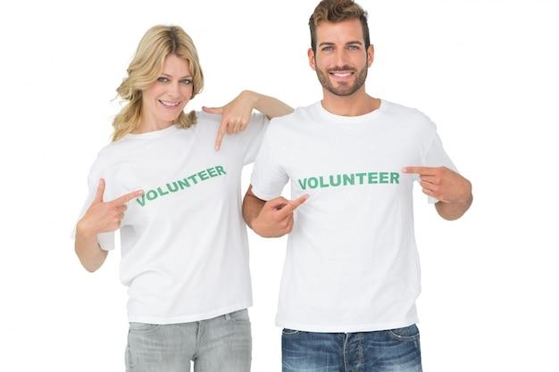 Retrato de dos voluntarios felices apuntando a sí mismos